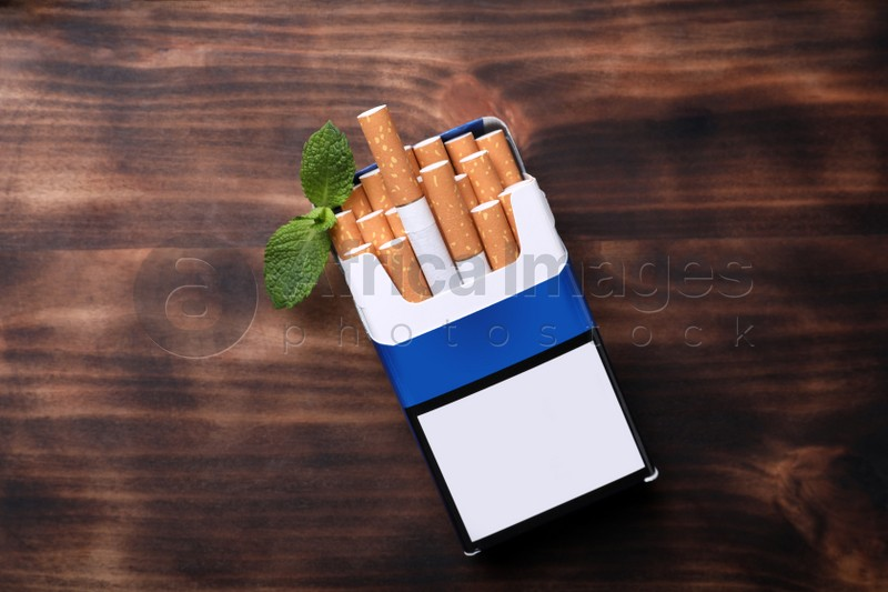 Pack of menthol cigarettes and mint leaves on wooden table, flat lay