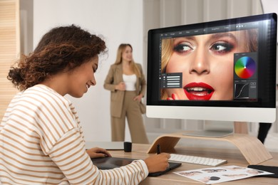 Professional African American retoucher working with graphic tablet at desk in photo studio