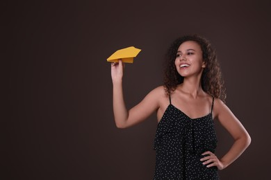 Beautiful African-American woman playing with paper plane on brown background. Space for text