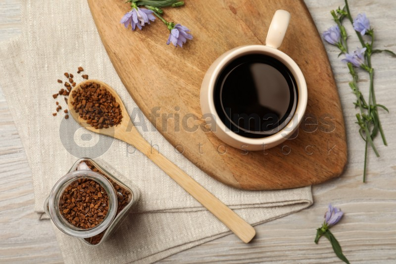 Cup of delicious chicory drink, granules and flowers on white wooden table, flat lay
