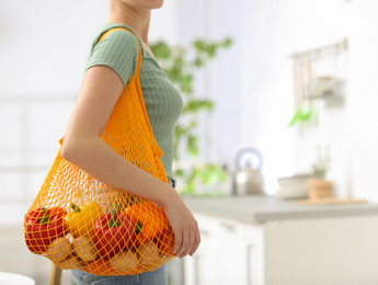 Woman with net bag full of fruits and vegetables in kitchen, closeup. Space for text