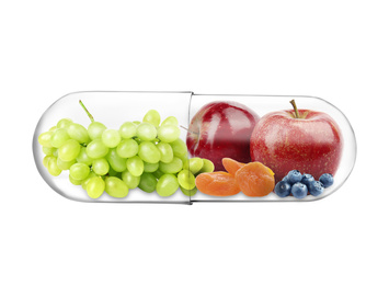 Transparent capsule with different fruits and berries rich in vitamins on white background