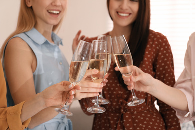 Young ladies clinking glasses of champagne, closeup. Women's Day