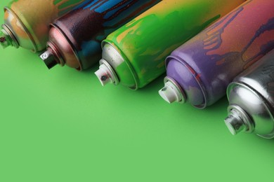 Used cans of spray paints on green background, closeup with space for text. Graffiti supplies