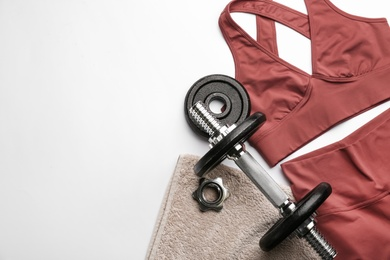 Sportswear, towel and dumbbell on white background, flat lay with space for text