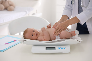 Doctor weighting cute baby in clinic, closeup. Health care