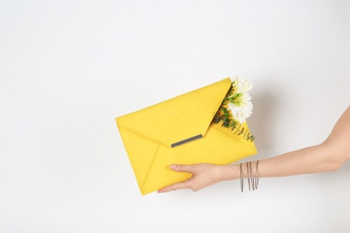 Woman with stylish clutch and spring flowers against light background, closeup