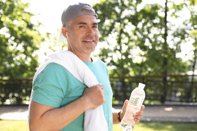 Handsome mature man with bottle of water in park. Healthy lifestyle