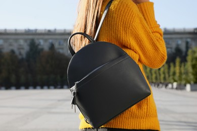 Woman with stylish black backpack on city street, closeup