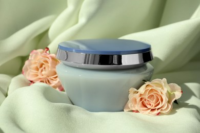 Jar of hair care cosmetic product and beautiful flowers on light green fabric
