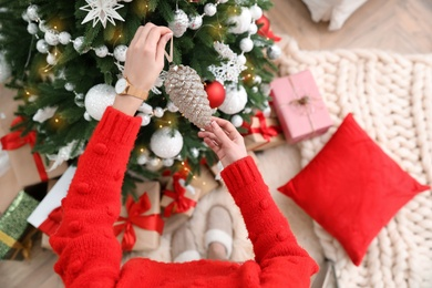 Woman decorating Christmas tree at home, top view