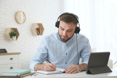 Young man taking notes during online webinar at table indoors