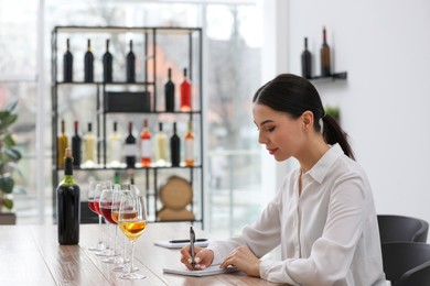 Sommelier making notes during wine tasting at table indoors