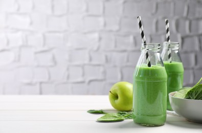 Tasty fresh green smoothie near ingredients on white wooden table, space for text