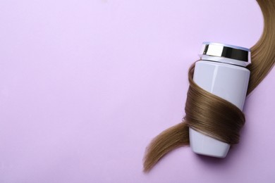 Bottle wrapped in lock of hair on violet background, top view with space for text. Natural cosmetic product