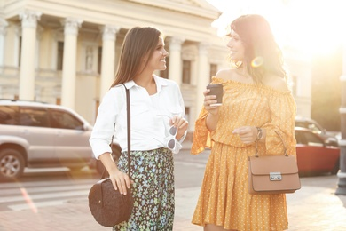 Young women with stylish bags on city street