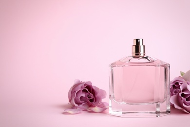 Bottle of perfume and beautiful roses on pink background. Space for text
