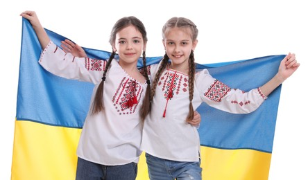 Happy girls in national clothes with flag of Ukraine on white background