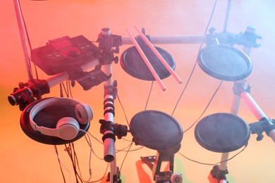 Modern electronic drum kit and smoke on orange background, color toned. Musical instrument