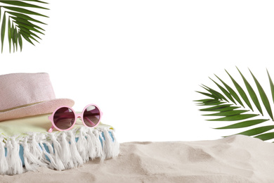 Folded towel, hat and sunglasses on sand against white background, space for text. Beach objects