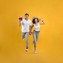 Couple of tourists with tickets and passports running on yellow background