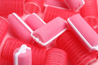 Different hair curlers on pink background, closeup. Styling tool