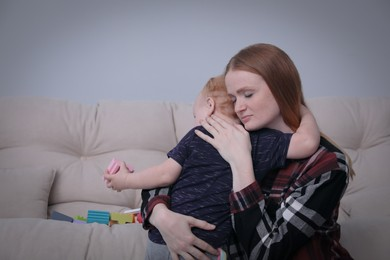 Young single mother hugging her child in living room