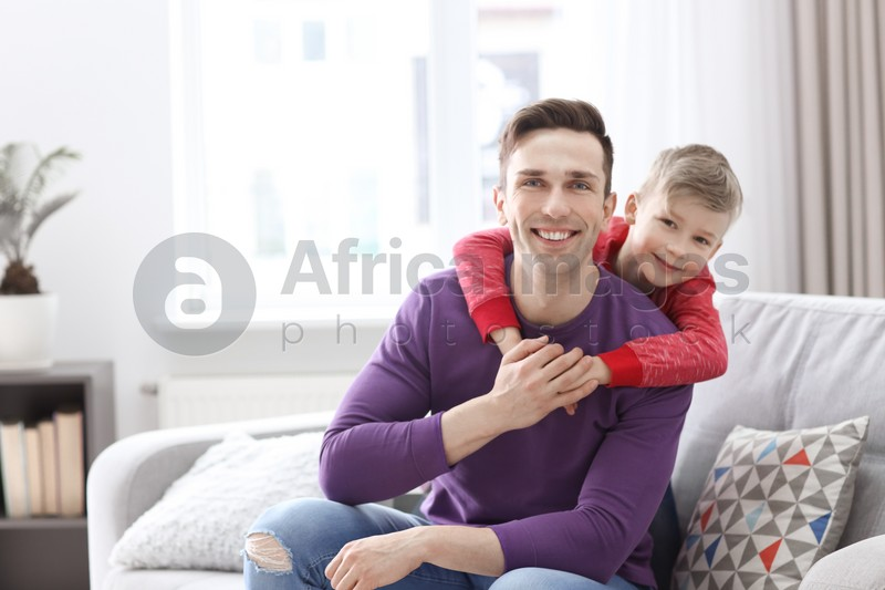 Dad and his son sitting on sofa at home