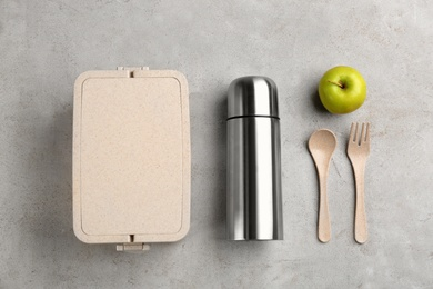 Thermos, lunch box and apple on light grey table, flat lay
