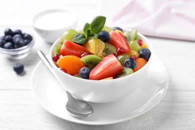 Delicious fresh fruit salad in bowl on white wooden table