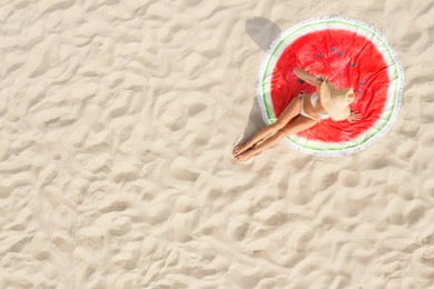 Woman sunbathing on round beach towel at sandy coast, aerial view. Space for text