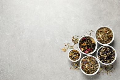 Flat lay composition with different dry teas on light grey table, space for text