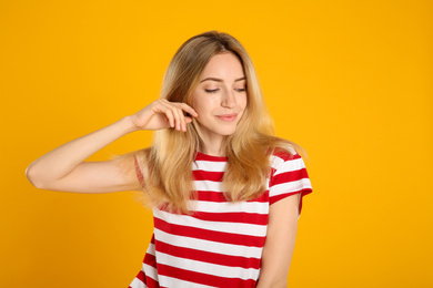 Portrait of beautiful young woman with blonde hair on yellow background