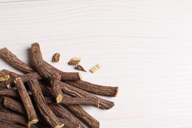 Dried sticks of liquorice root on white wooden table, space for text