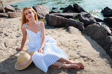 Beautiful young woman with straw hat near sea on sunny day in summer