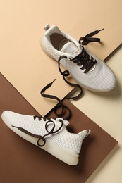 Stylish sneakers with brown shoe laces on color background, flat lay