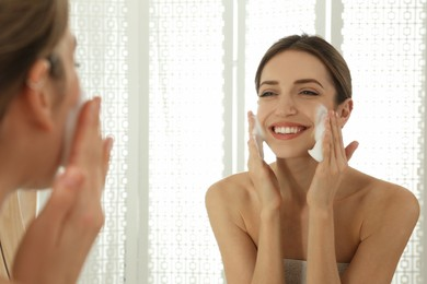 Young woman applying cleansing foam onto her face near mirror in bathroom
