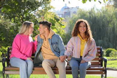 Man flirting with another woman while holding girlfriend's hand on bench in park. Love triangle