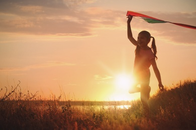 Cute little child with kite running outdoors at sunset. Spending time in nature
