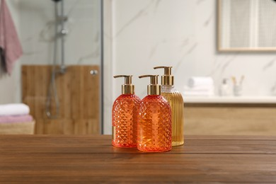 Different glass dispensers with liquid soap on wooden table in bathroom