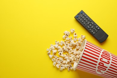 Remote control and cup of popcorn on yellow background, flat lay. Space for text