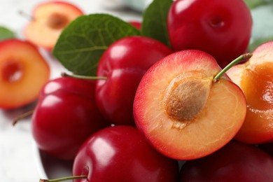 Delicious ripe cherry plums with leaves on table, closeup