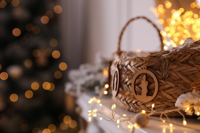 Fireplace mantel with wicker basket and Christmas lights against blurred background. Interior element