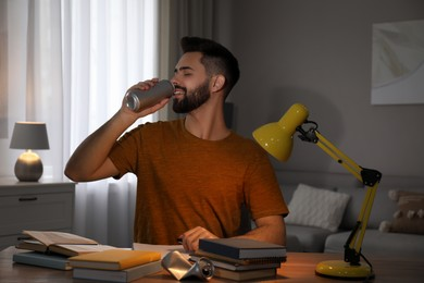 Young man with energy drink studying at home