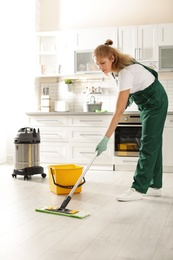 Professional janitor cleaning floor with mop in kitchen