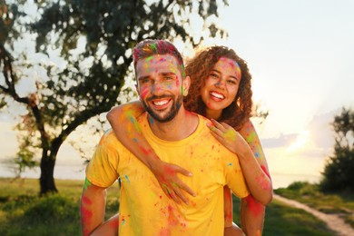Happy couple covered with colorful powder dyes outdoors. Holi festival celebration