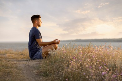 Man meditating near river on sunny day, space for text