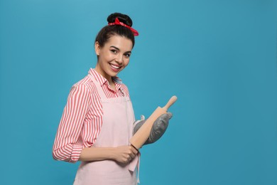 Young housewife in oven glove holding roller pin on light blue background, space for text