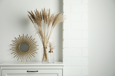 Stylish decorative vases on commode in room