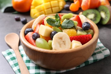 Delicious fresh fruit salad on grey table